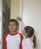 pic of measuring height  - Sister measuring brother - JPG