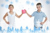 Brother and sister holding piggy bank together against snowflakes and fir trees