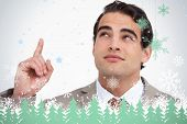 Close up of salesman looking and pointing up against snowflakes and fir trees in green