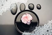 Composite image of snowflake frame against pink and white carnation floating in a black bowl with aligned black pebbles above it