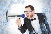 Geeky businessman shouting through megaphone against snowflake frame