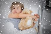 Composite image of cute girl hugging teddy bear in hospital bed against snow falling