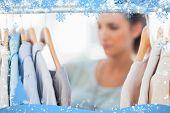 Fashion woman choosing clothes on clothes rail against snow