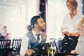 Handsome businessman ordering food from waitress against snow