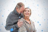 Happy mature couple in winter clothes against snow falling