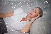 Composite image of businesswoman sleeping on couch against snow