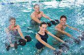 Happy fitness class doing aqua aerobics with foam dumbbells against snow