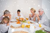 Composite image of Family saying grace before eating a turkey against snow falling