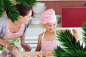 Cheerful mother and her daughter baking in a kitchen against digitally generated fir tree branches