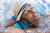 Handsome shirtless man listening to music poolside against snow