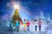 Composite image of cute children smiling at camera against snowy landscape with fir trees