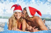 Man giving kiss to partner wearing christmas hats against snow