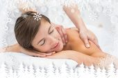 Attractive young woman receiving shoulder massage at spa center against fir tree forest and snowflakes