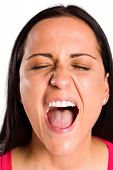 Angry young brunette shouting in close up on white background