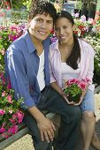 Couple Sitting Among Flowers At Plant Nursery, Portrait