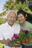 image of senior men  - Asian Senior couple holding flowers outdoors  - JPG