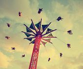 stock photo of toned  -  a fair ride shot with a long exposure at dusk toned with a retro vintage instagram filter  - JPG