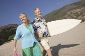Senior Couple with surfboard smiling on beach