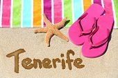 Tenerife beach travel background concept. TENERIFE written in sand with water next to beach towel, summer sandals and starfish. Summer and sun vacation holidays on Canary Islands, Spain.