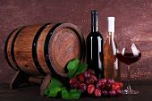 Wine in bottles and in goblet, grapes and wooden barrel on wooden table on wooden background