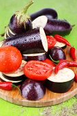 Chopped aubergines with tomatoes and chilly pepper on cutting board on wooden background