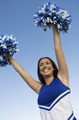 Smiling Cheerleader rising pom-poms (portrait) (low angle view)