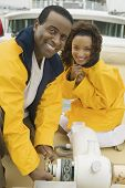 Couple wearing yellow anoraks on yacht (portrait)