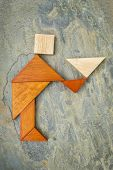 abstract of a butler, waiter or servant figure built from seven tangram wooden pieces, a traditional Chinese puzzle game; slate rock background, the artwork copyright by the photographer