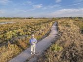 a senior male with a remote controller is flying a drone - a selfportrait shot from a low flying quadcopter drone