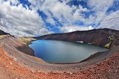 Iceland in July. Oval blue lake in the crater of the volcano cooled down. Steep banks of the lake of red rhyolite