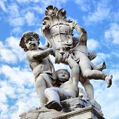 The statue of angels with embleb od the city on Square of Miracles in Pisa near Leaning Tower, Italy