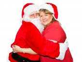 Santa and his wife hugging each other.  Isolated on white.