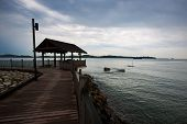 Wooden boardwalk by the sea with rolling dark clouds.