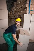 Warehouse worker loading up a pallet in a large warehouse