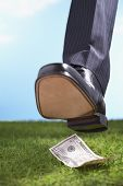 Businessman stepping on fifty-dollar bill in grass close-up of foot