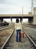 Young woman walking on train tracks