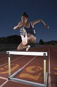 Female track athlete clears a hurdle
