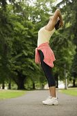 Side view of woman stretching in park