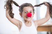 Portrait of playful little girl wearing clown nose holding pigtails at home