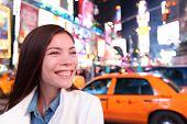 Woman in New York City, Manhattan, Times Square at night. Smiling happy joyful Multiethnic Asian Caucasian young urban professional in her 20s.