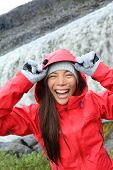 Woman laughing in raincoat by Dettifoss waterfall on Iceland. Excited girl in hardshell visiting tourist attractions and landmarks on Diamond Circle. Dettifoss waterfall in Vatnajokull National Park.