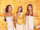 Happy girlfriends relaxing in sauna.