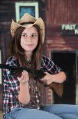 A pretty teen cowgirl holding her rifle in front of a rustic western building.
