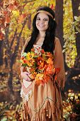 A beautiful teen Indian maiden holding a bouquet of flowers that she's found near a colorful autumn woods.