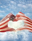 American flag on heart shaped hands, in front of bright sky