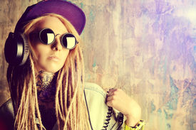 image of dreadlock  - Trendy teenage girl with blonde dreadlocks listening to music on headphones - JPG