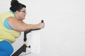 foto of exercise bike  - Overweight Woman on Exercise Bike side view - JPG