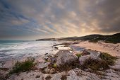 Late Evening Landscape Of Ocean Over Rocky Shore Heavy Clouds Blowing In