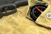 image of handgun  - Modern Handgun and Compass On The Weathered Backpack - JPG