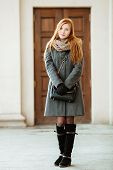 Portrait of young beautiful redhead woman wearing coat and scarf posing outdoors